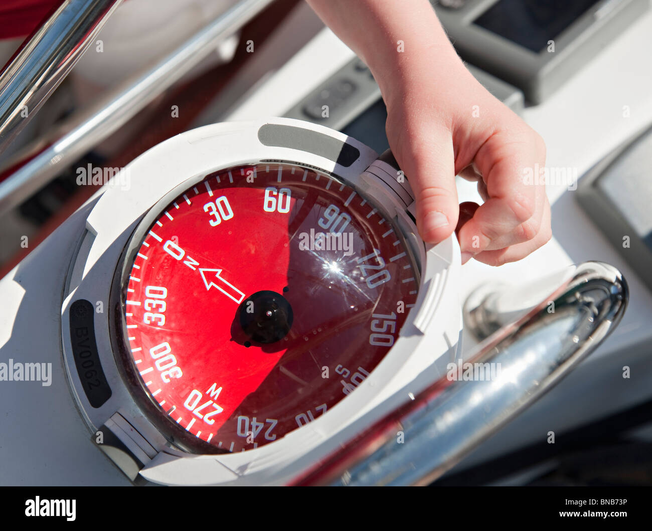 Boy with compass on yacht - Stock Image