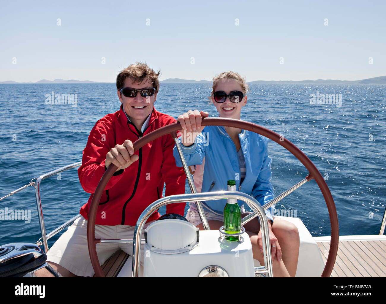 Man and woman steering yacht - Stock Image