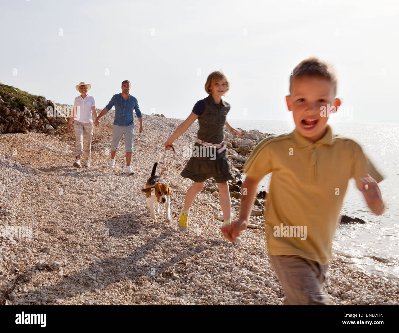 Family with dog running at the beach - Stock Image