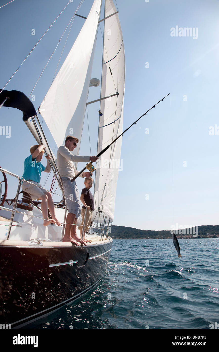 Father and sons fishing on yacht - Stock Image