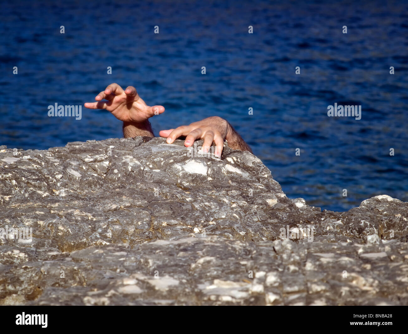Castaway finds salvation on the rocky shore of an unknown island. Stock Photo