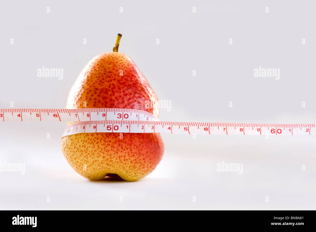 pear oppress by measurement tape to symbol as a diet - Stock Image
