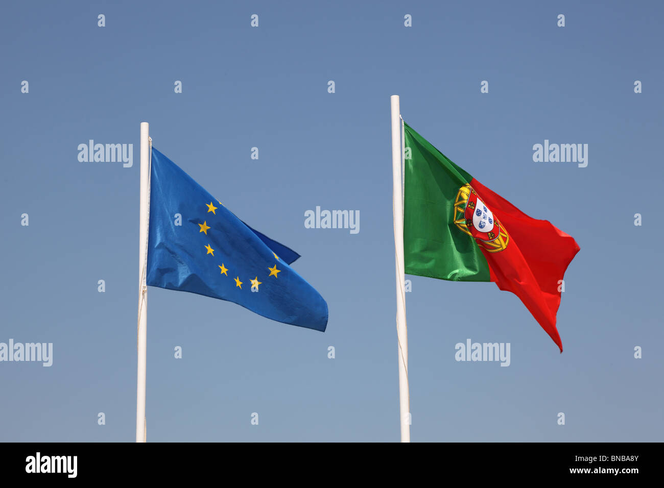 Portuguese and European flags against blue sky - Stock Image