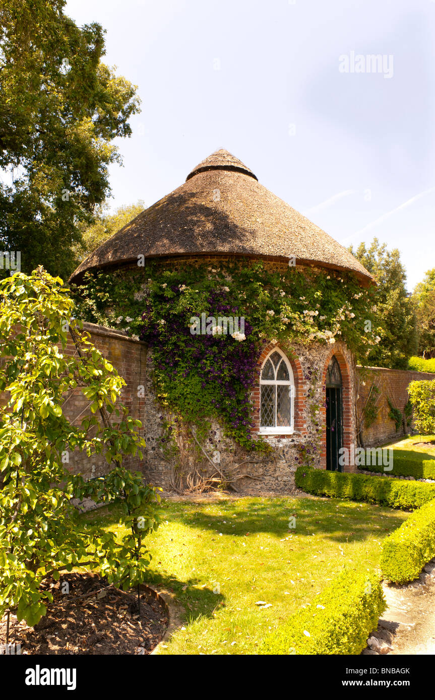Potting shed with thatched roof built into the wall of the walled ...