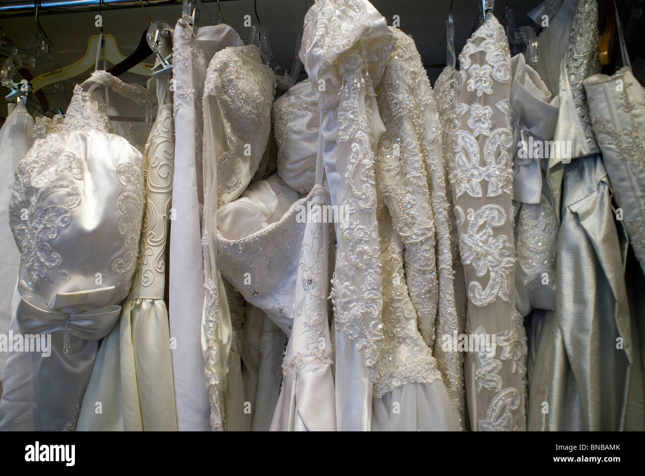 Previously owned wedding dresses awaiting brides are on display in a ...