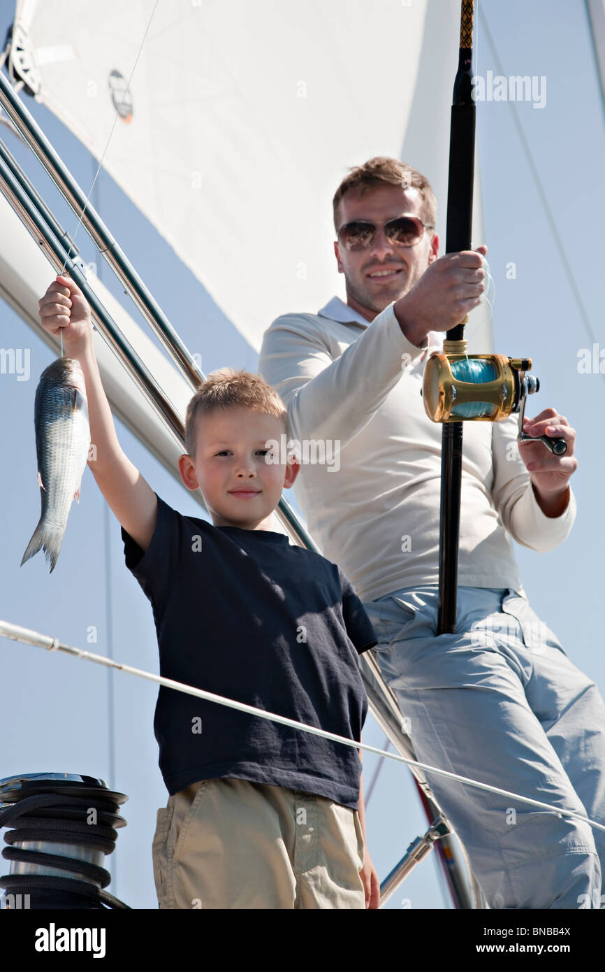 Father and son fishing on yacht - Stock Image
