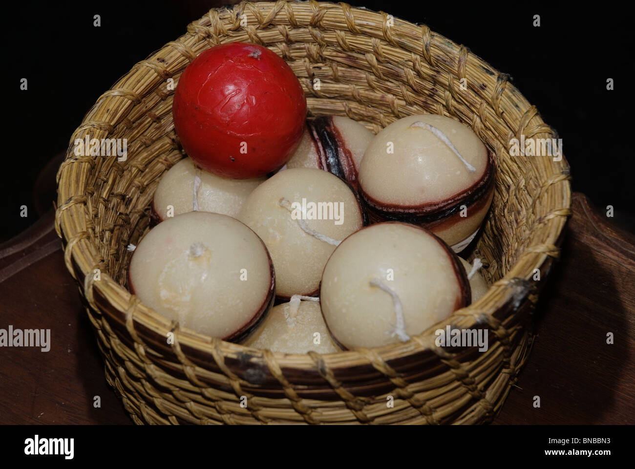 High angle close-up basket of candles, one red among many white. - Stock Image