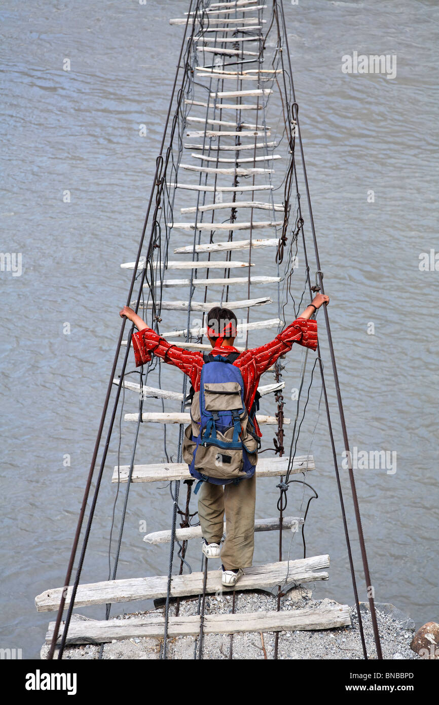 Man crossing a suspension bridge across the Hunza River, Hunza Valley, Karakorum, Pakistan Stock Photo