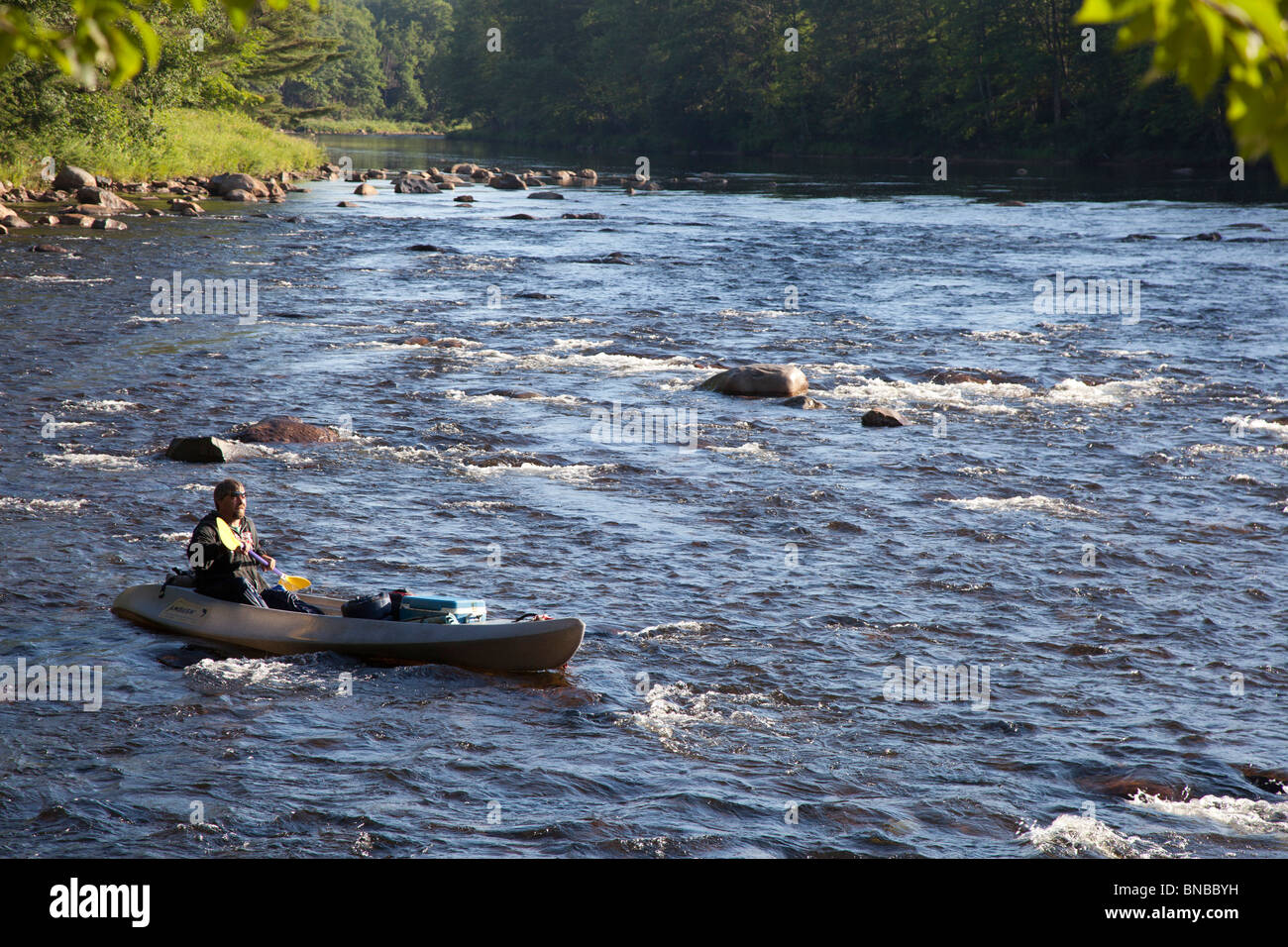 A Man Paddles Canoe Kayak Hybrid Through Rapids In The Early Morning On Pemigewasset River