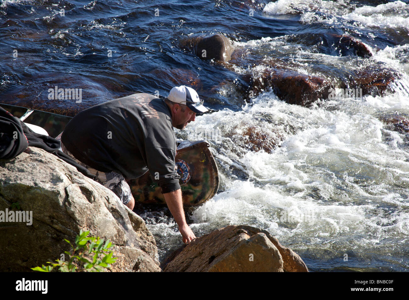 Campton, New Hampshire - A man wading on the Pemigewasset River in the White Mountains guides his canoe through - Stock Image