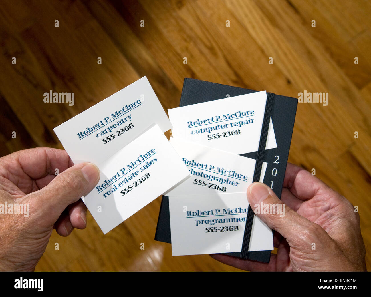 Close Up Of Hands Holding Multiple Business Cards With Varied Stock