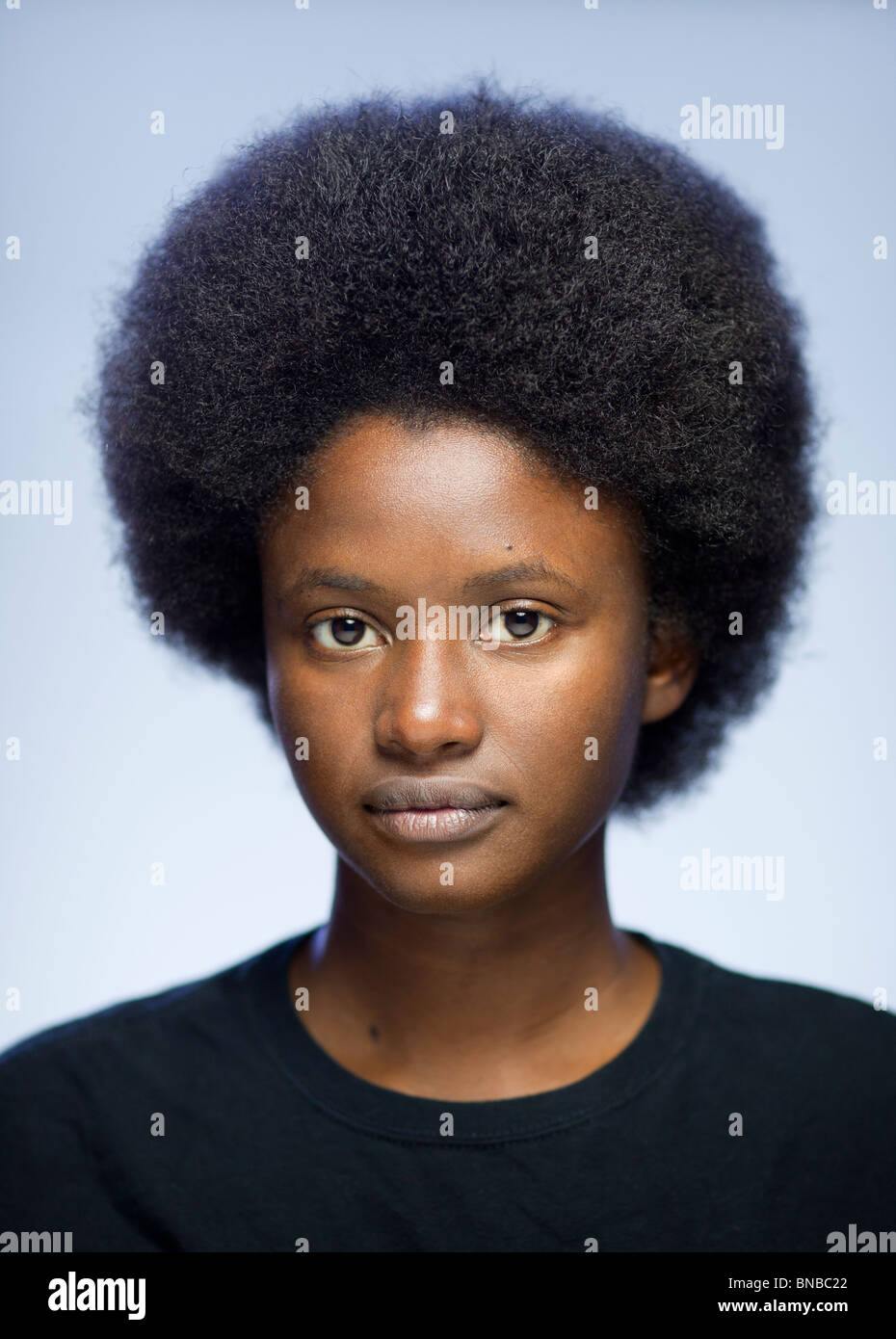 Close-up portrait of young woman of African descent with an afro staring at camera - Stock Image