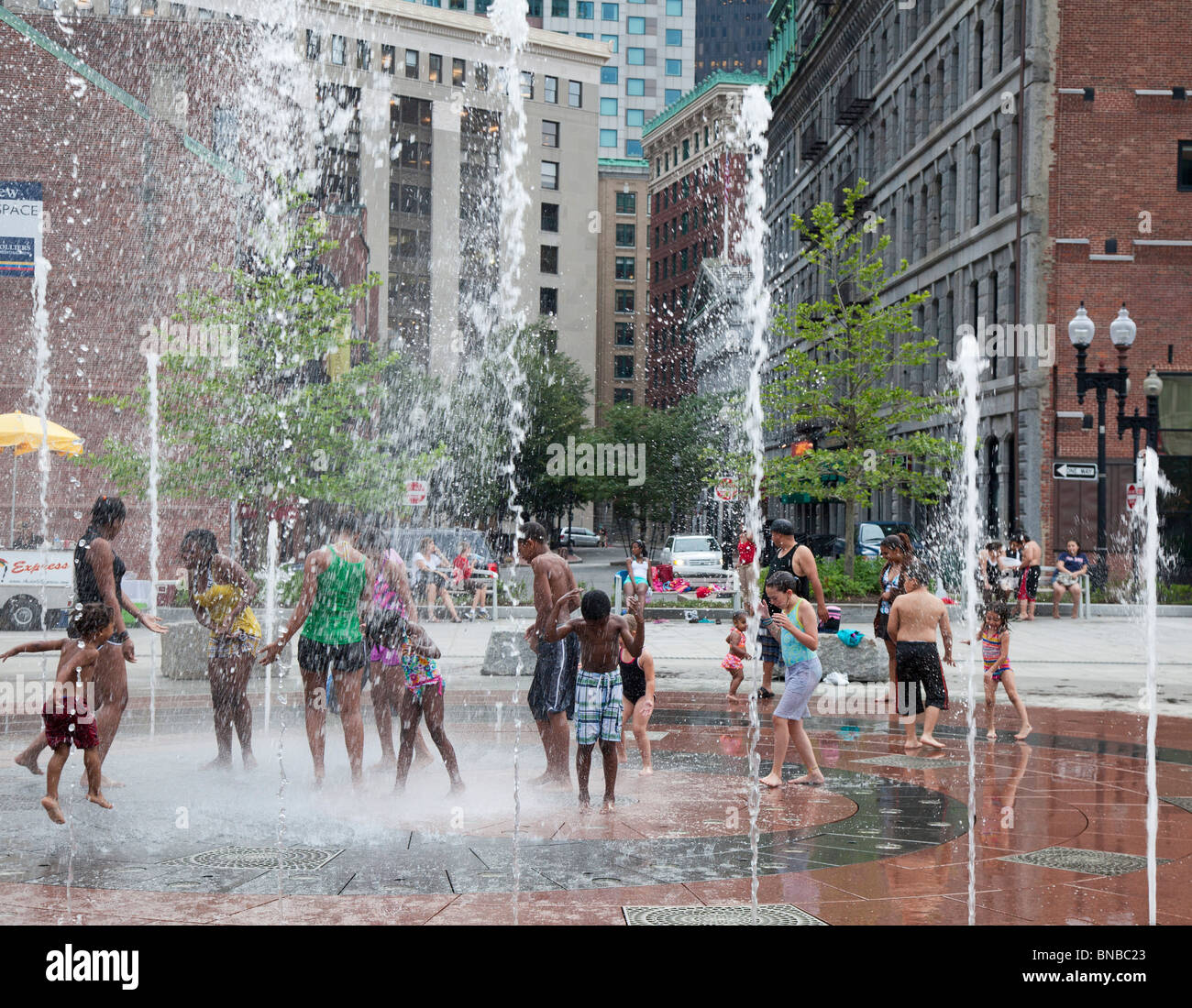 Boston, Massachusetts - Children play in a fountain near the Boston waterfront on a hot summer evening. - Stock Image