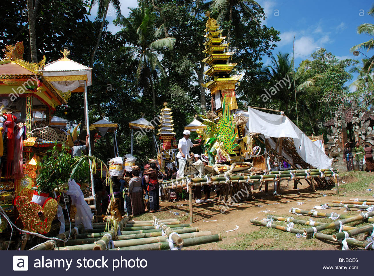 Ornate funeral biers and coffins at a mass Hindu cremation ceremony women carry offerings on their heads Bangli - Stock Image
