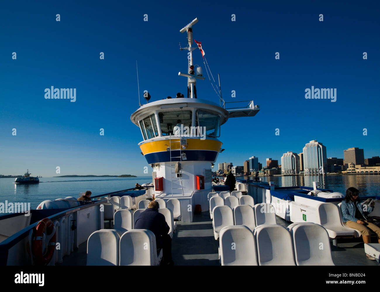 A ferry ride from Dartmouth to Halifax with Purdy's Wharf, the city skyline, and a ferry heading in the opposite - Stock Image