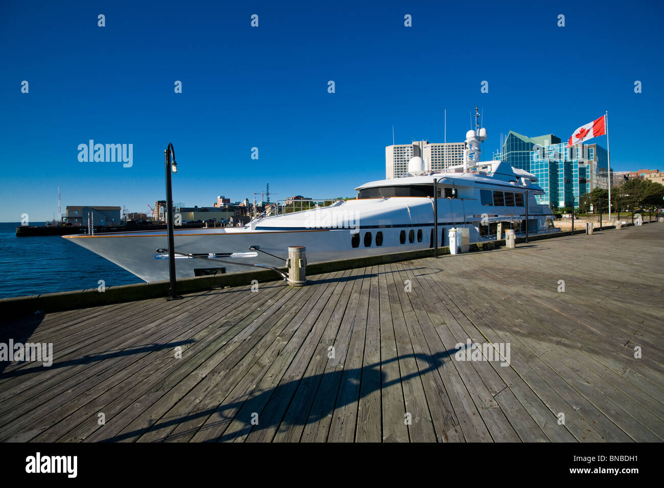 A private yacht is tied up alongside a pier in front of Summit Place in Halifax, Nova Scotia. - Stock Image