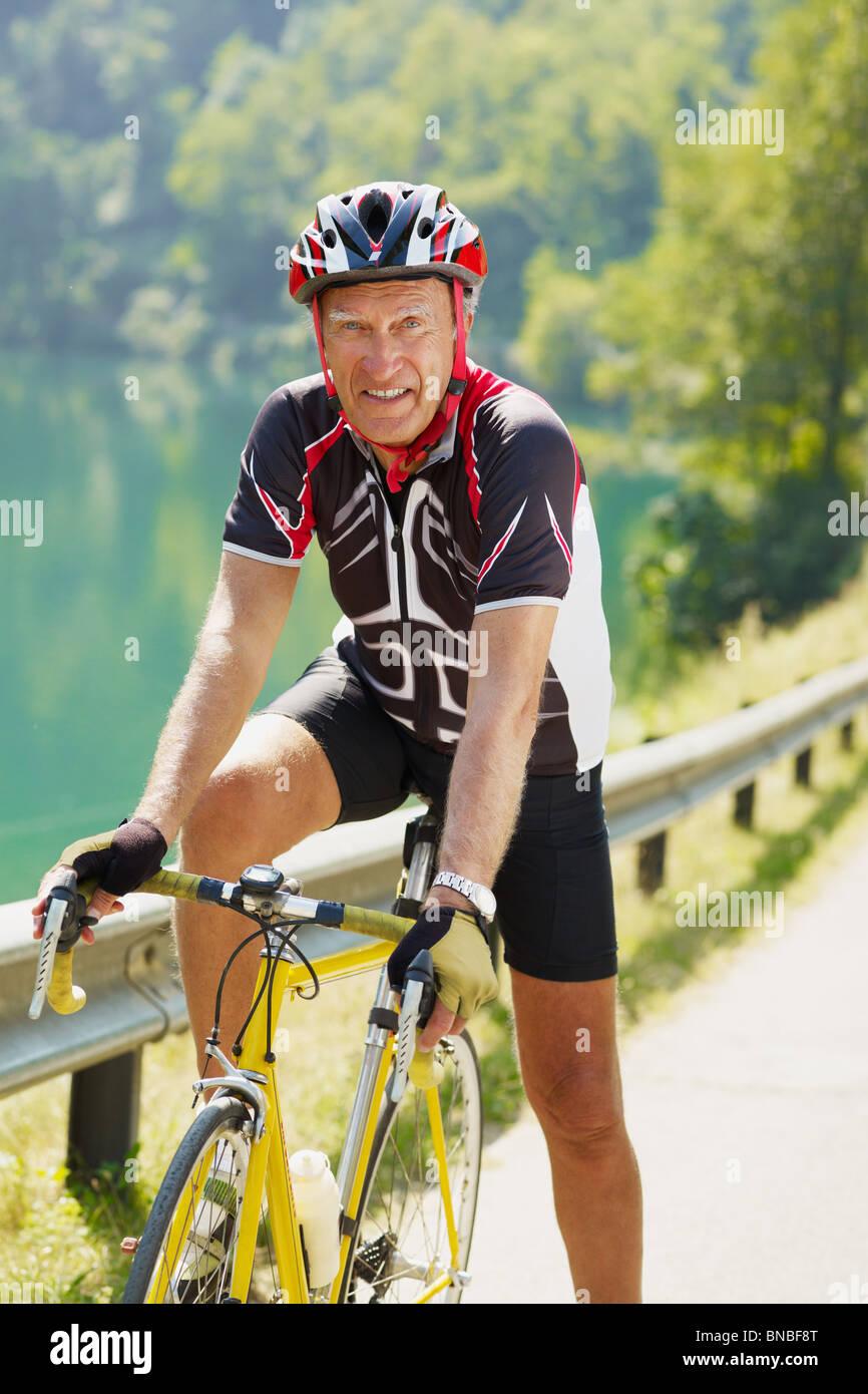 senior man on road bike, looking at camera. - Stock Image