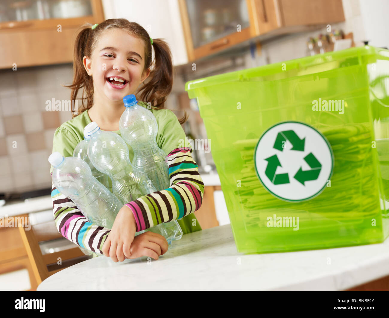 Girl holding plastic bottles for recycling - Stock Image