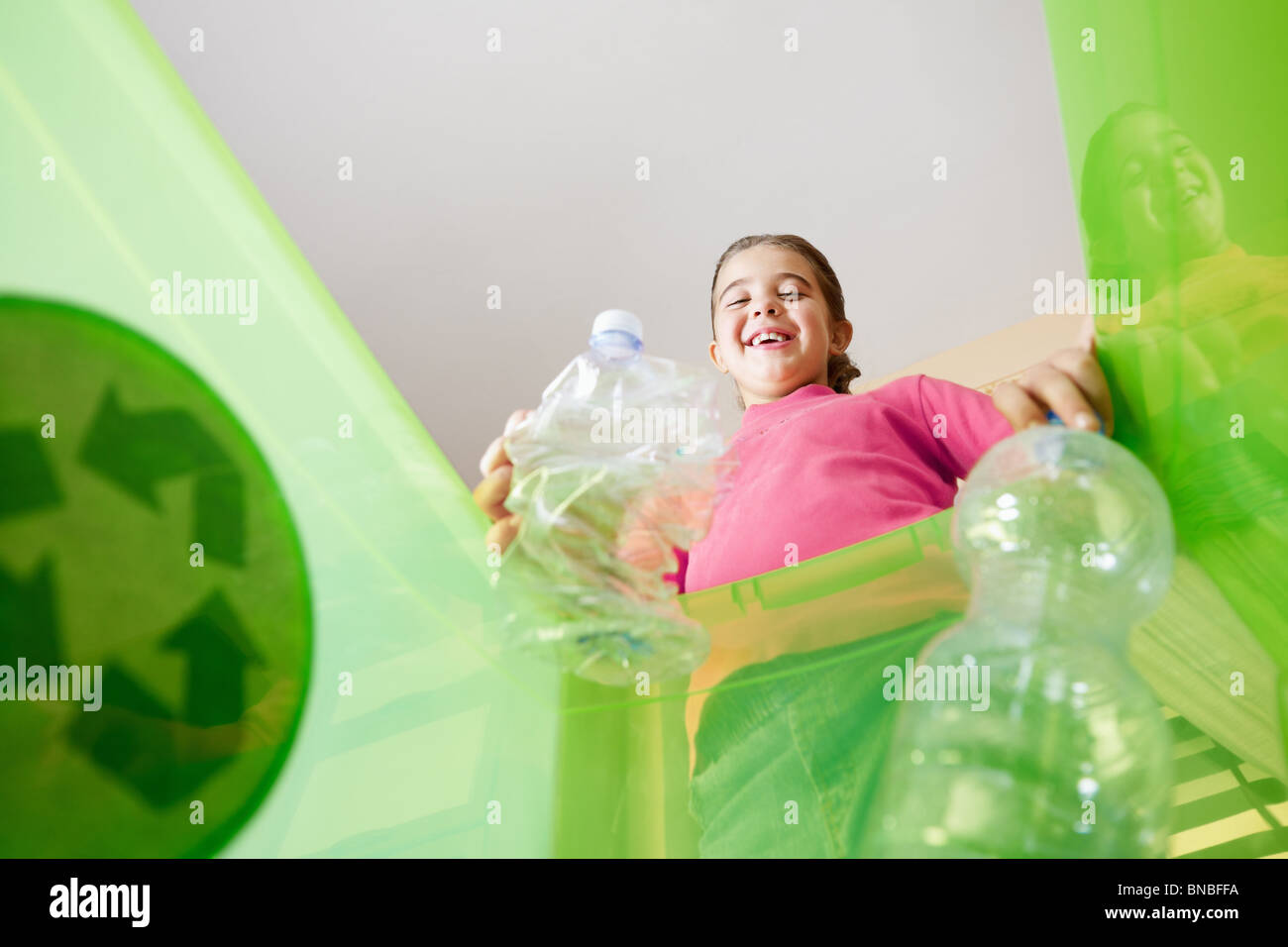 Girl holding plastic bottles for recycling, viewed from inside recycling bin. Copy space - Stock Image