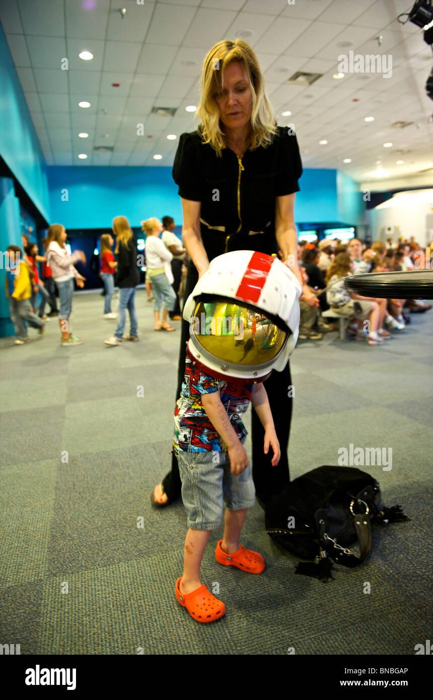Three year old boy trying on a heavy astronaut helmet , space centre, Houston, Texas, U.S.A Stock Photo
