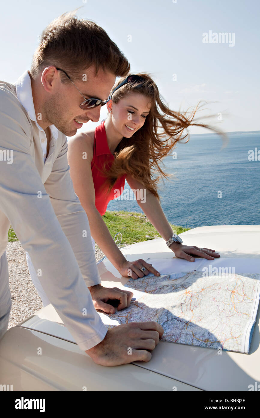 Couple with oldtimer looking at map - Stock Image