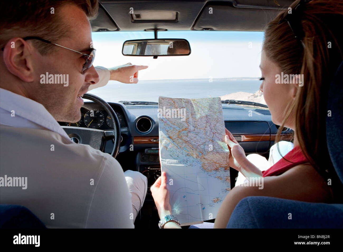 Couple looking at map in car by sea - Stock Image