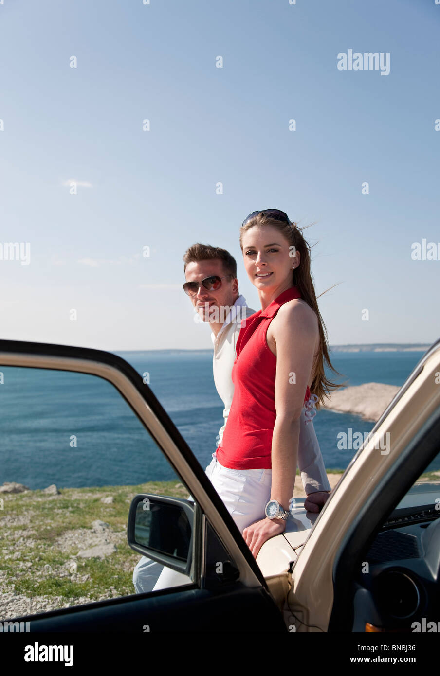 Couple with oldtimer by sea - Stock Image