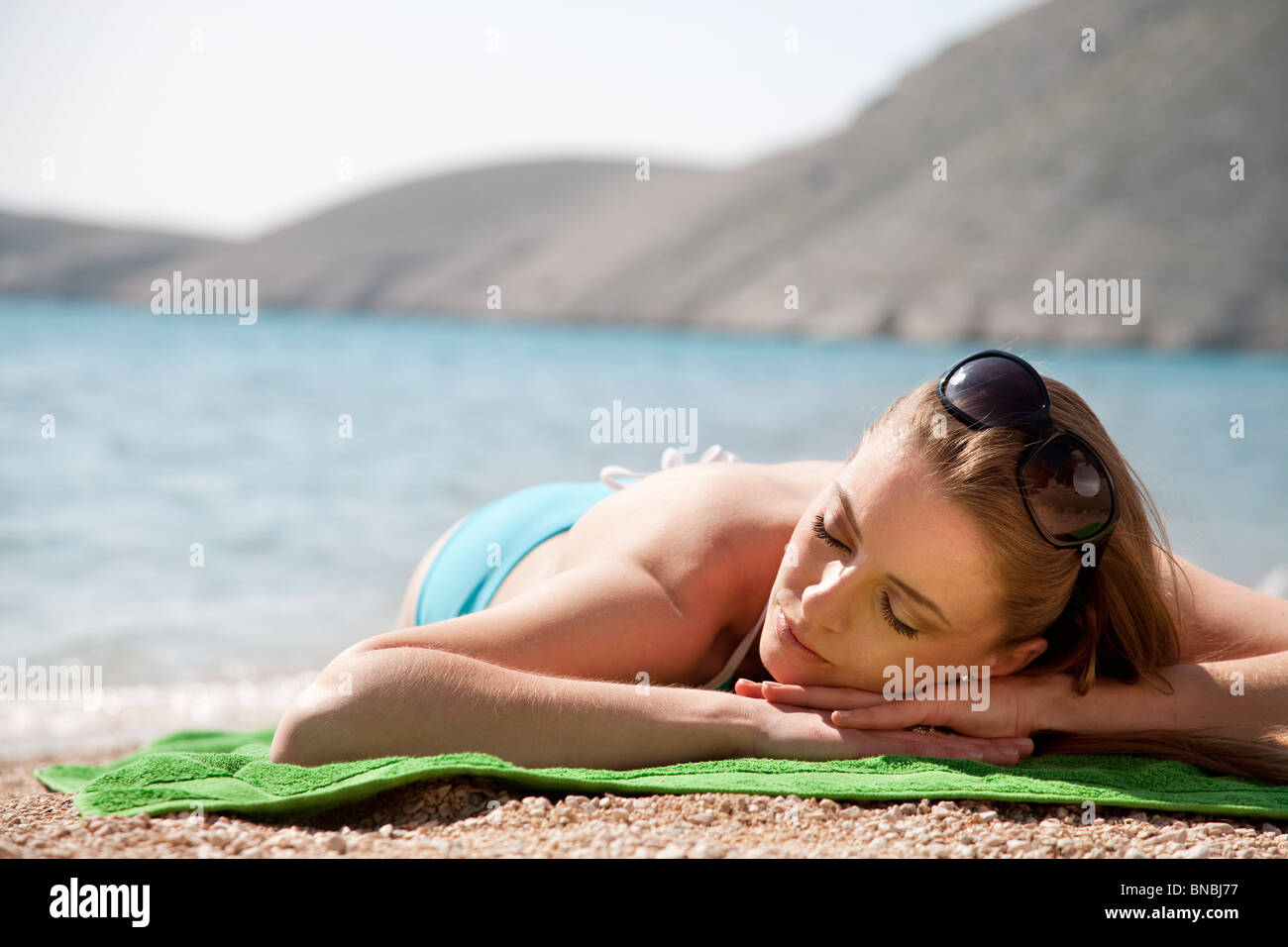 Woman sunbathing at the beach - Stock Image