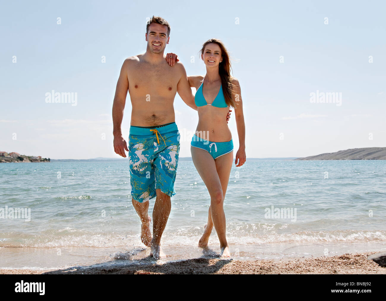 Couple coming out of water at beach - Stock Image