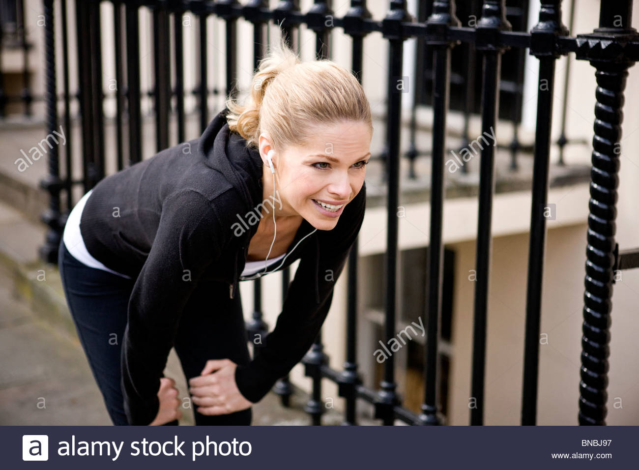 A female runner recovering, wearing headphones - Stock Image