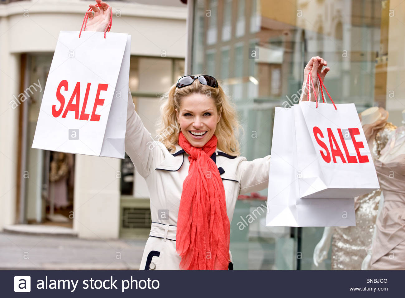 A mid adult woman holding up some sale bags, smiling - Stock Image