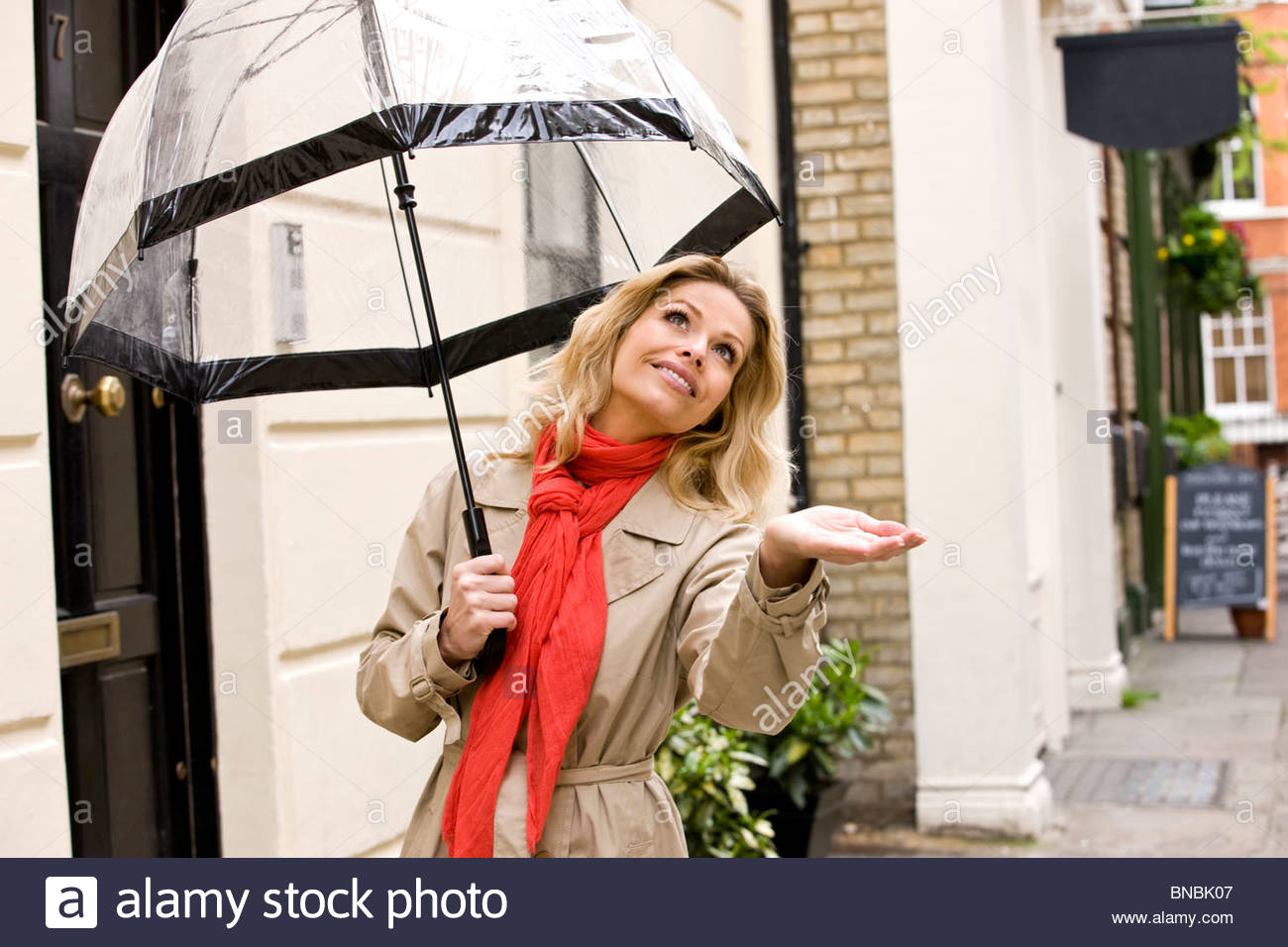 A mid adult woman holding an umbrella, checking for rain - Stock Image