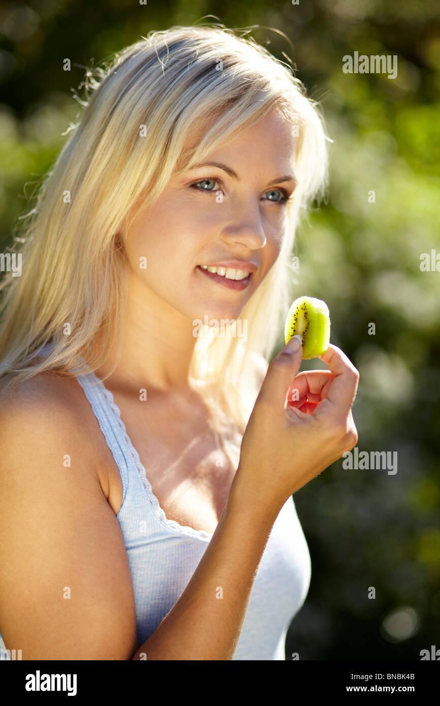 Girl eating Kiwi fruit - Stock Image