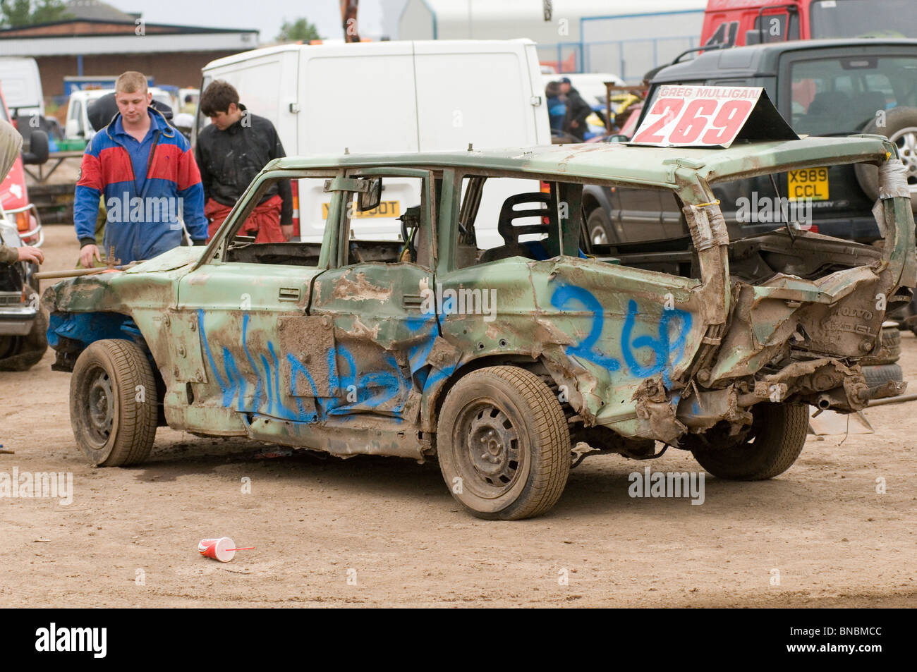 banger racing mechanic driver hitting scrap junk old car with sledgehammer sledge hammer repair repairing maintenance - Stock Image