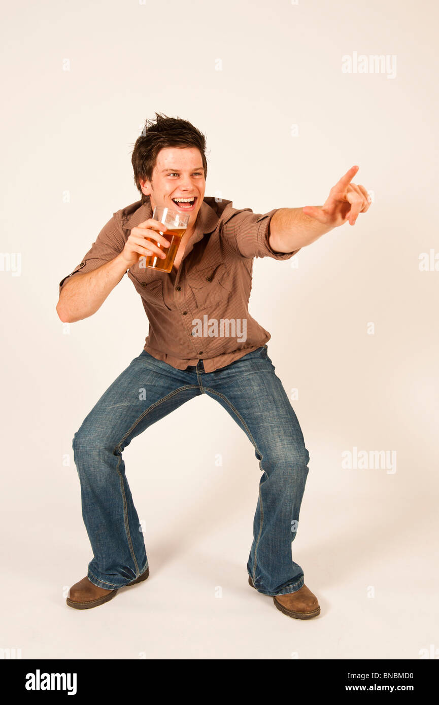 Happy young man drinking a pint of beer lager - Stock Image