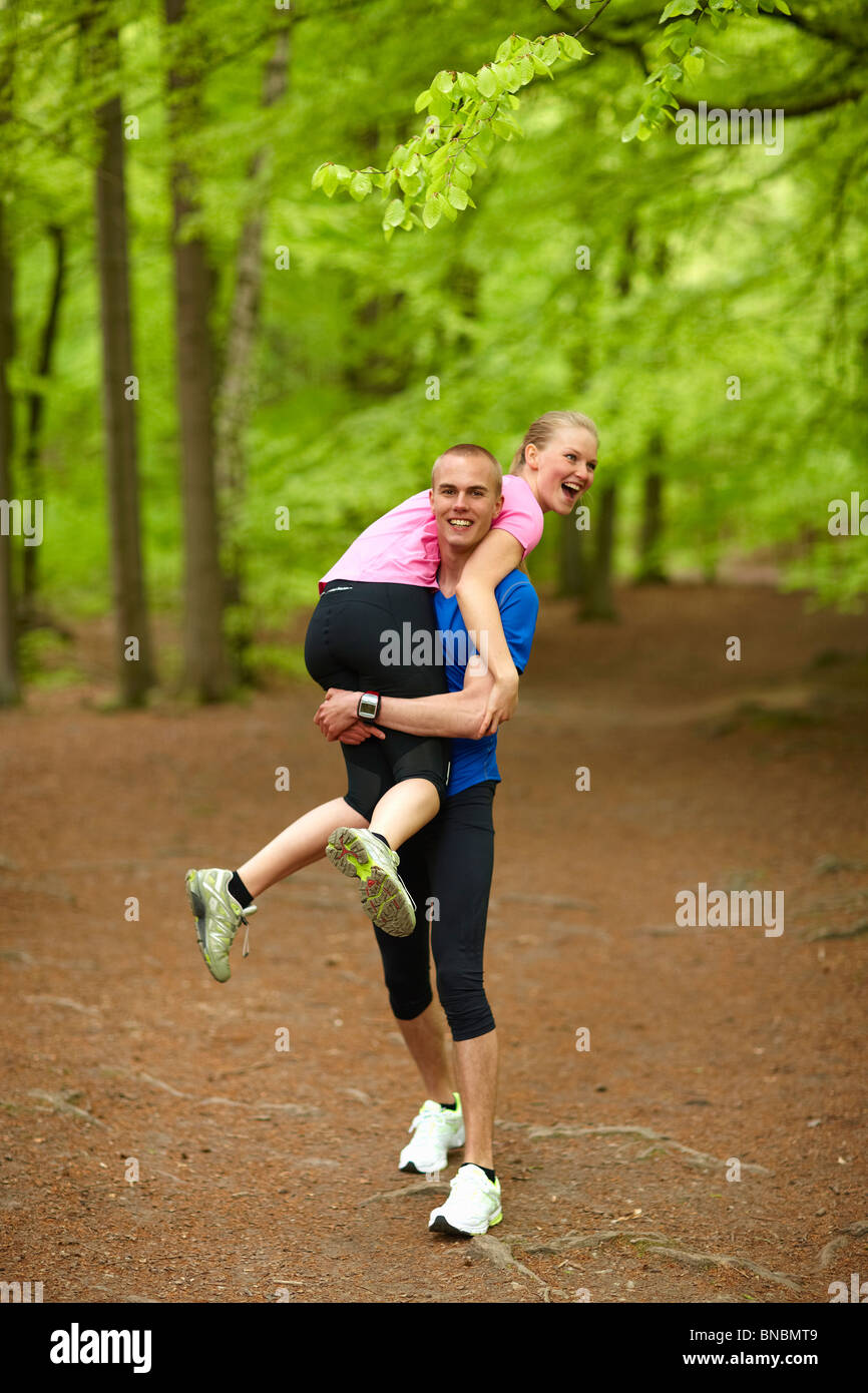 Couple running in forest, having fun Stock Photo