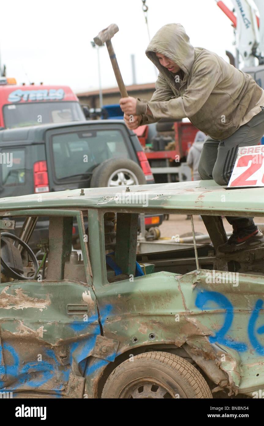 banger racing mechanic driver hitting scrap old car with sledgehammer - Stock Image
