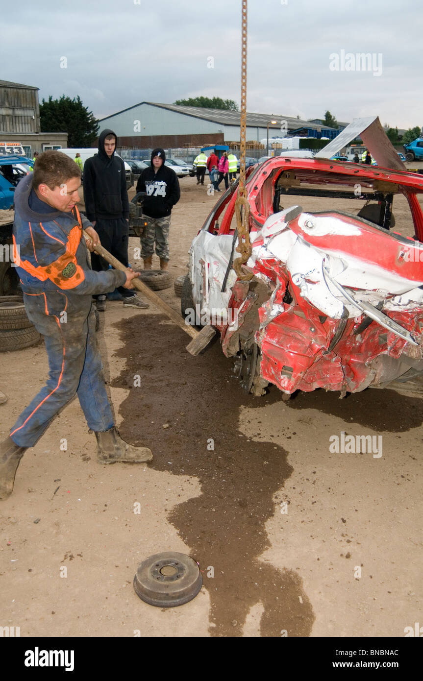 banger racing mechanic driver hitting scrap junk old car with sledgehammer sledge hammer repair repairing maintance - Stock Image