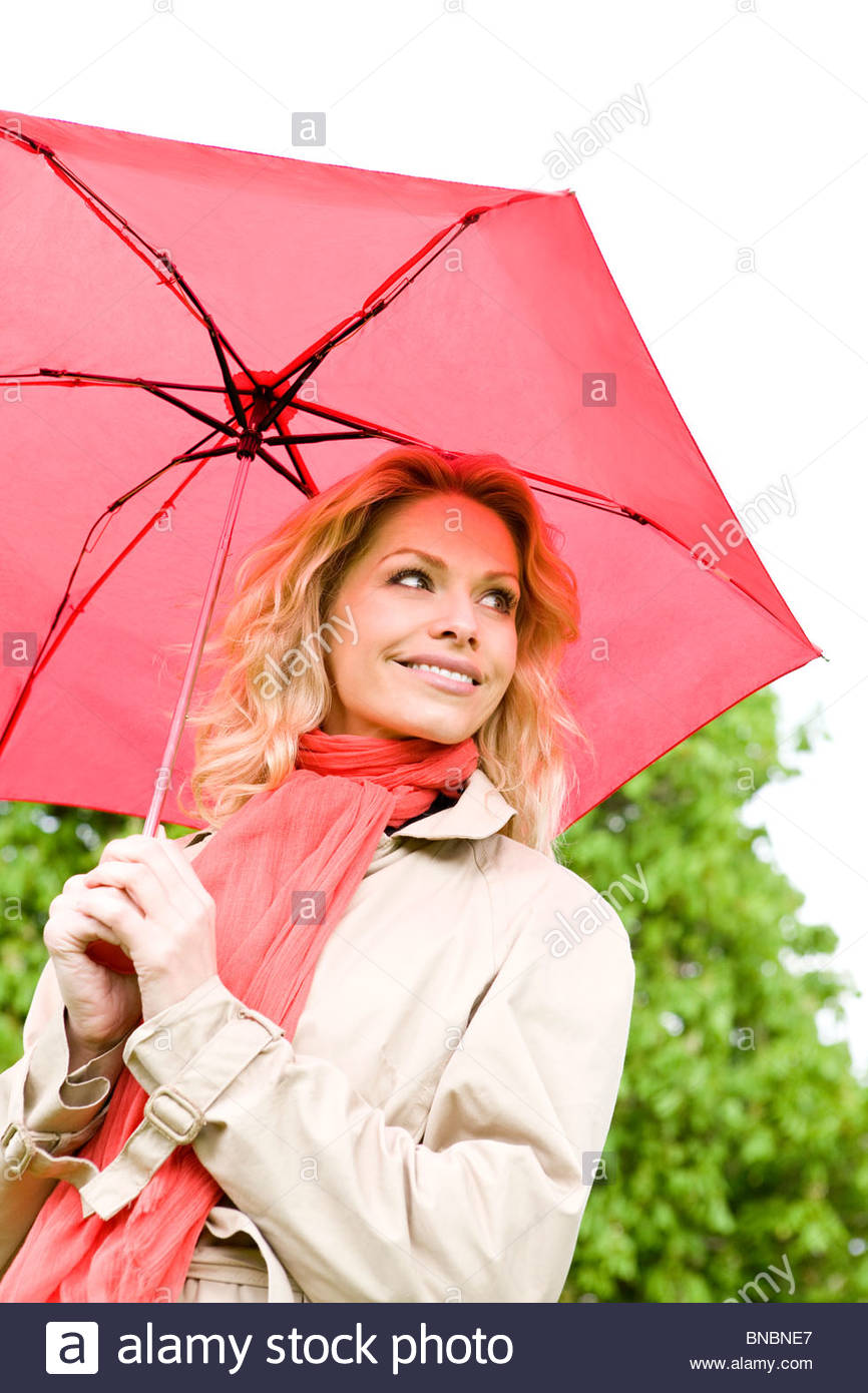 A mid adult woman holding a red umbrella - Stock Image