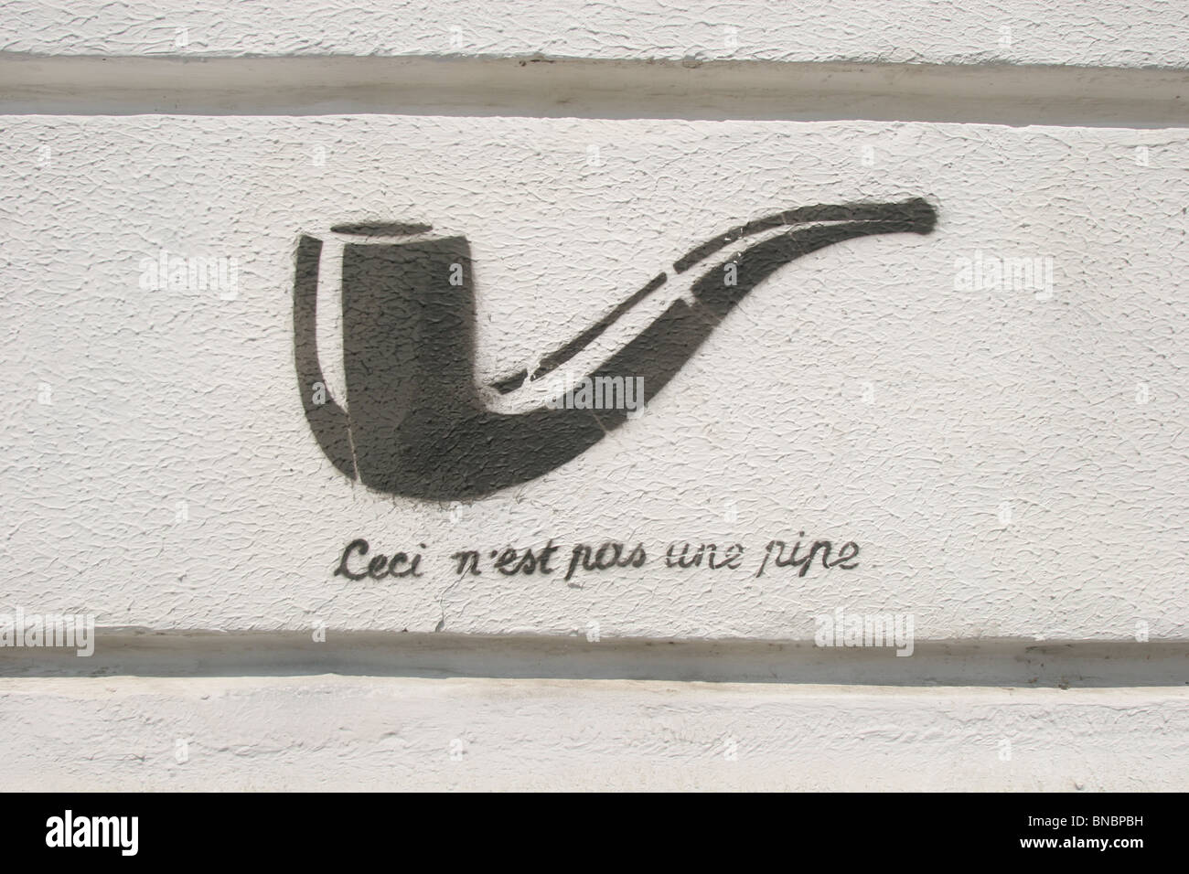 Stenciled graffiti art representation of Rene Magritte's surrealist masterpiece 'Ceci n'est pas une - Stock Image