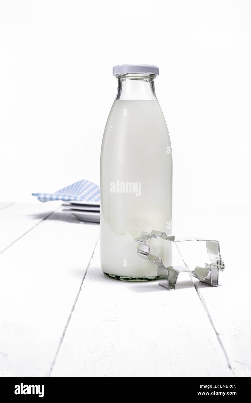 Milchflasche und kuhfoermige Ausstechform auf weissen Holztisch Stock Photo