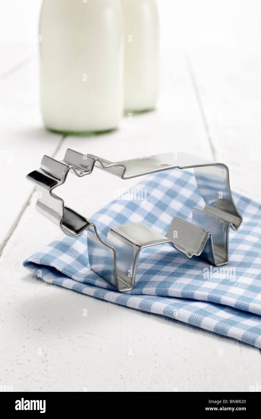 Kuhfoermige Ausstechform, im Hintergrund zwei Milchflaschen Stock Photo