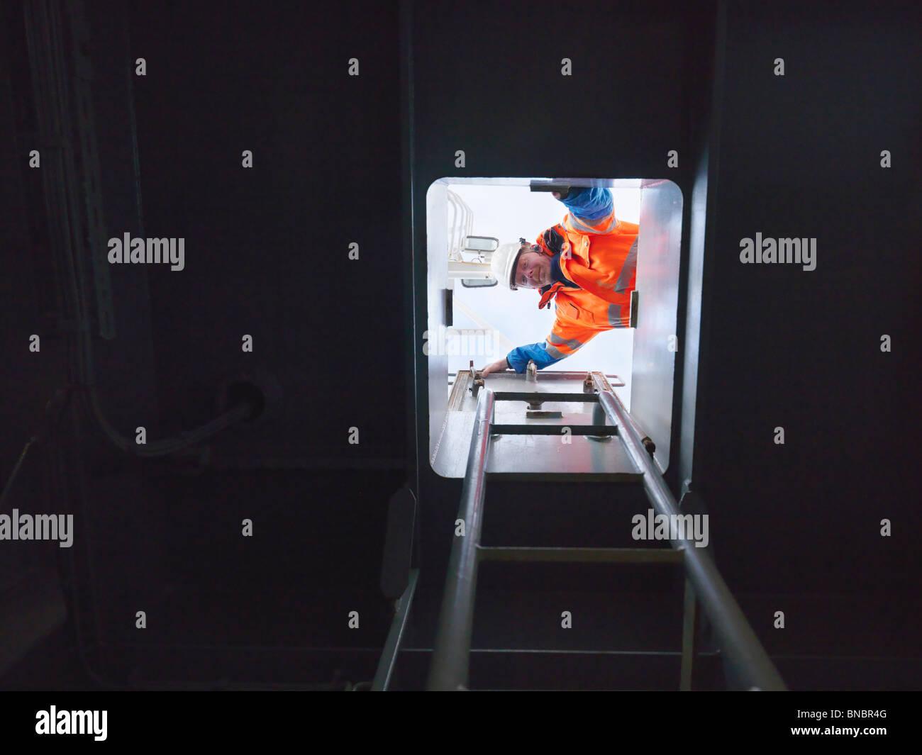 Sailor looking through hatch - Stock Image