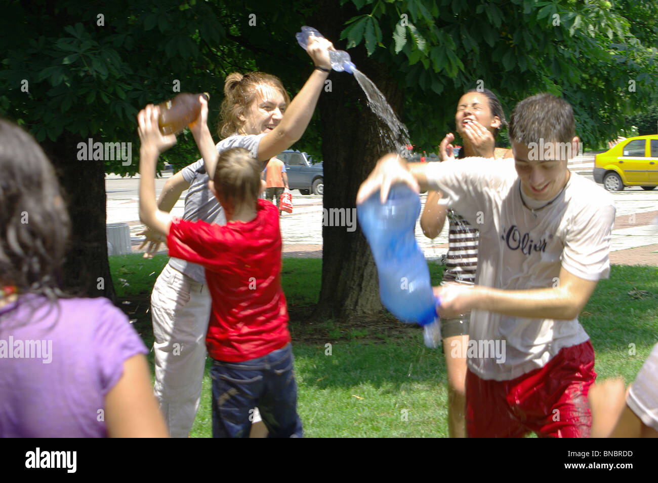 Hot summer day children play with water. - Stock Image