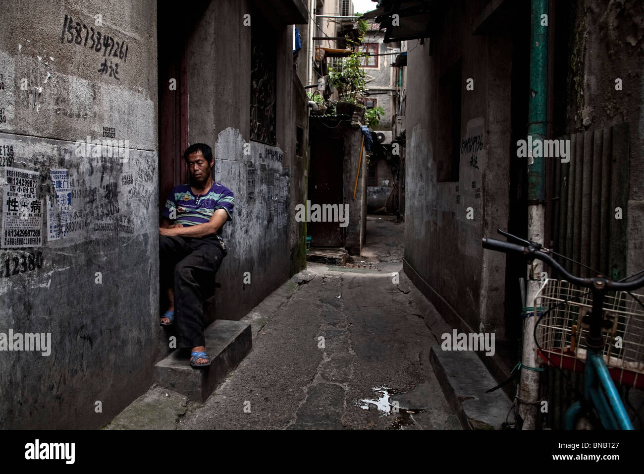 A cobbler waits for customers in an old neighbourhood in the Puxi area of Shanghai - Stock Image