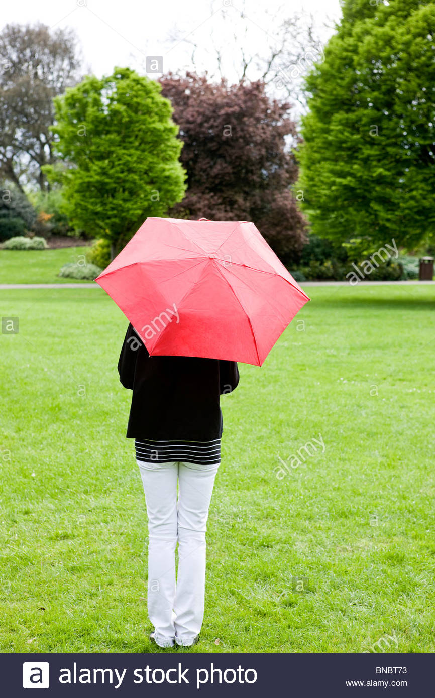 A woman standing in a park, holding a red umbrella, rear view - Stock Image