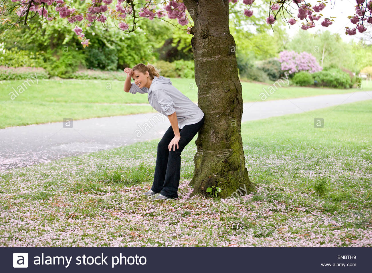 A female runner resting against a tree - Stock Image