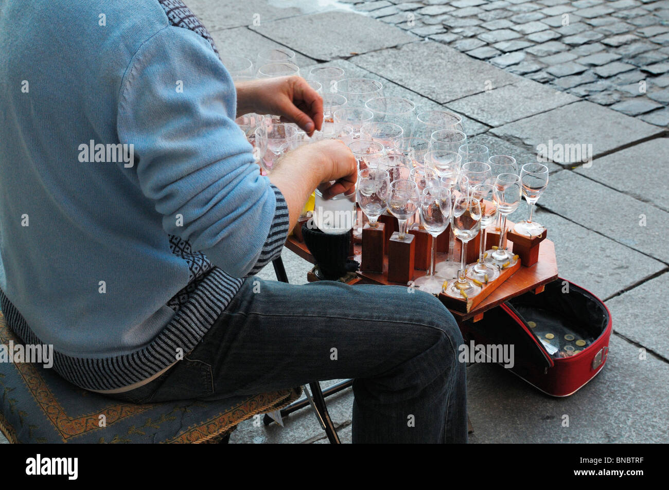 Street musician playing the 'glass harp' in central Madrid, Spain - Stock Image