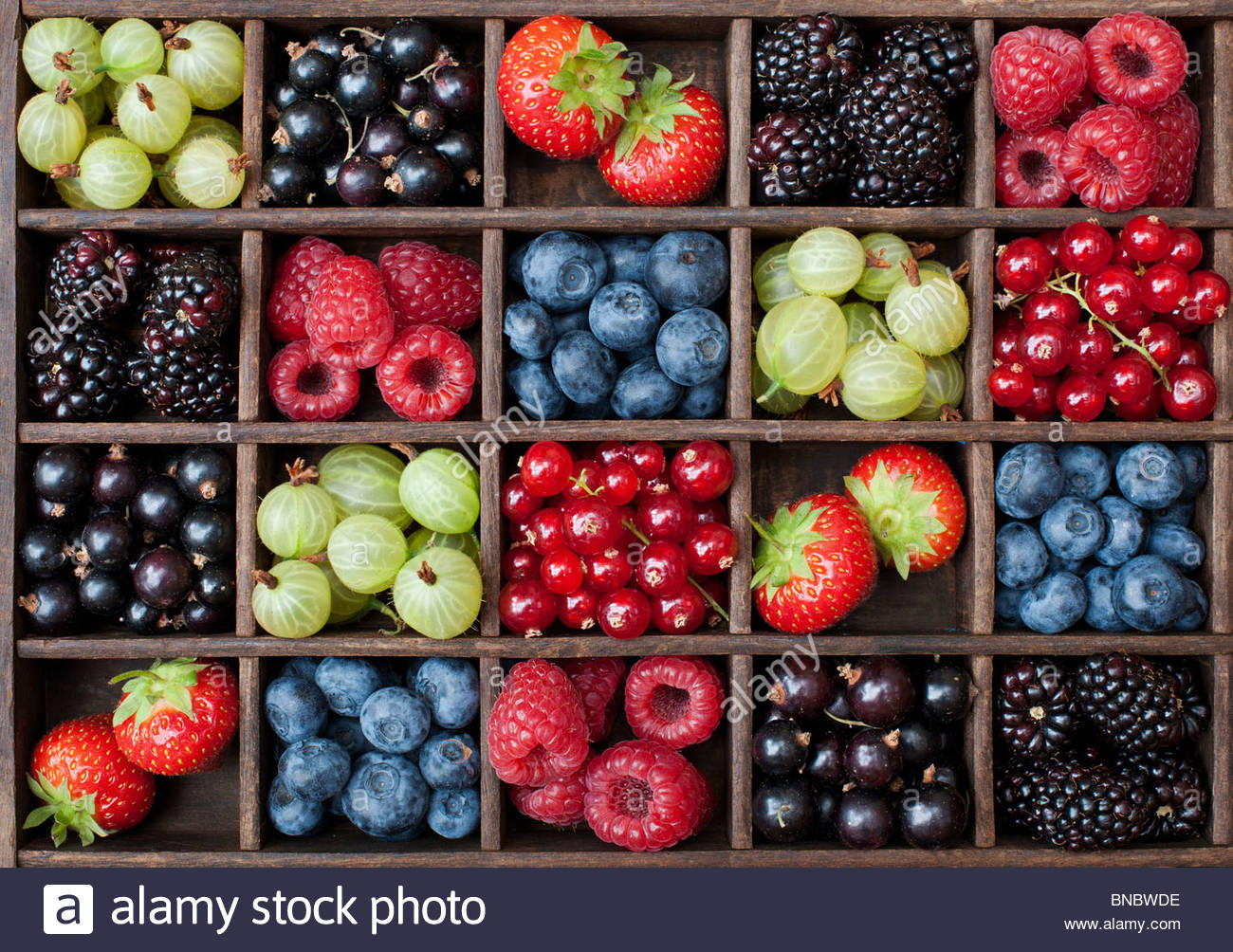 English summer berries and fruit in a wooden grid pattern. Flat lay photography from above - Stock Image
