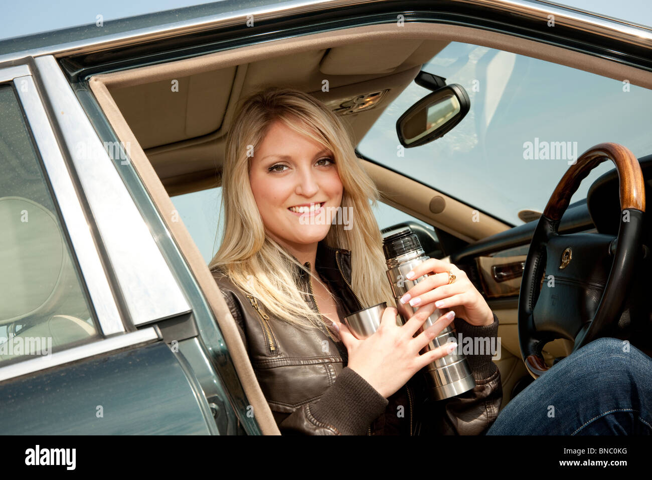 blonde woman sitting in parked car drinking tea thermos flask - Stock Image